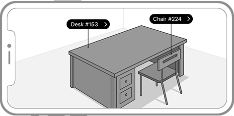 An iPhone screen in landscape showing the corner of a room viewed through the camera. In the room are two AR objects: a desk and a chair. Each object has a label in white text enclosed in a black oval. The oval is attached to the object by a vertical line. The label in each object ends with two spaces and a greater-than sign to indicate the label can be tapped for more information.